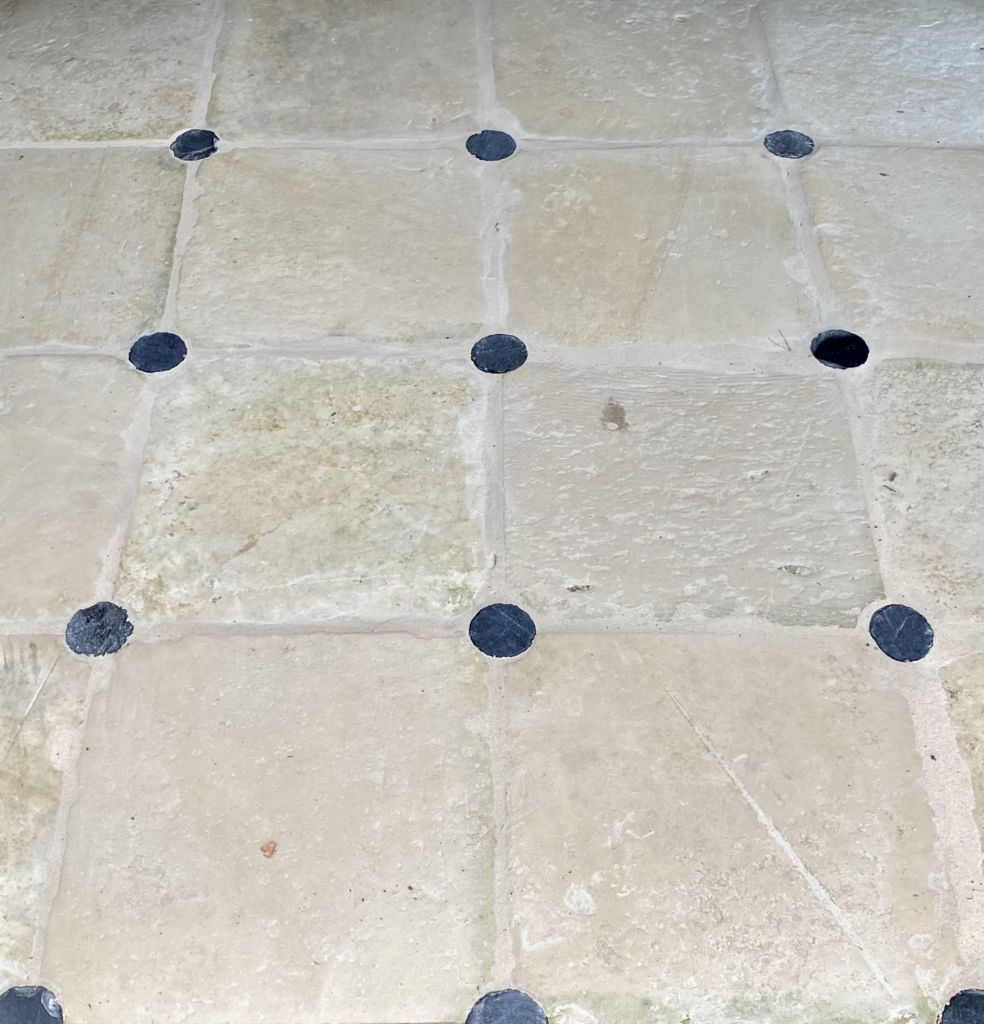 Antique limestone flooring with round cabochons